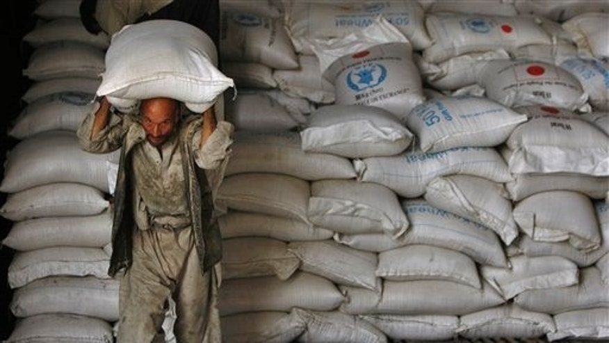 June 27: An Afghan man carries a sack of wheat from a UN World Food Programme warehouse. Due to budget constraints, on June 27th the UN announced that it would be force to cut food assistance to more than 3 million Afghan people.