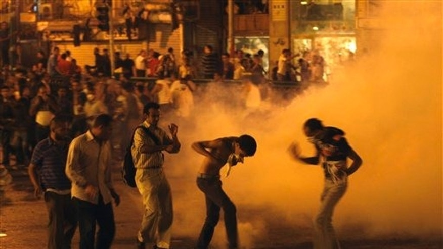 June 29: Demonstrators throw a tear gas grenade during clashes with the Egyptian security in Tahrir Square in Cairo, Egypt. Egyptian security forces firing tear gas clashed with protesters in central Cairo late Tuesday.