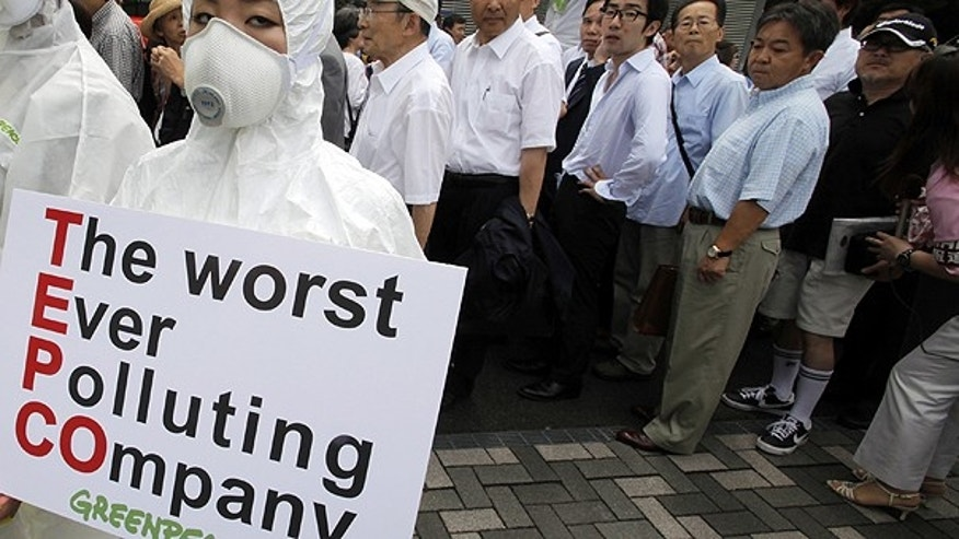June 28: A Greenpeace protester in protective gear holds a banner as shareholders, rear, arrive for the annual shareholders' meeting of Tokyo Electric Power Co. in Tokyo.