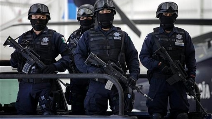 June 16. Mexican Federal Police stand guard at the presentation to the press of captured Zeta drug cartel member. On June 28 armed gunmen for the cartel killed the police chief of Santa Catarina, a northern Mexican city.