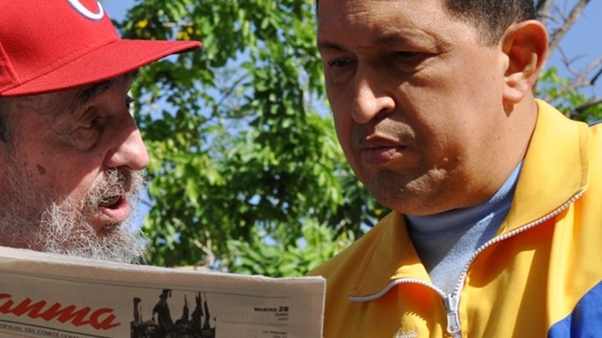 June 28: In this photo released by the state media Cubadebate web site, Cuba's Fidel Castro, left, and Venezuela's President Hugo Chávez look at Granma state newspaper at an unknown location in Havana, Cuba.(AP Photo/Cubadebate, Estudios Revolucion)