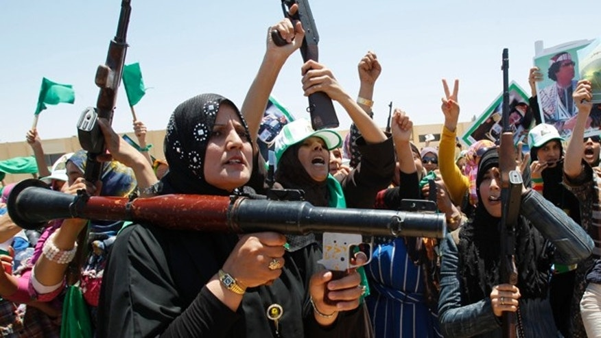 June 28: In this photo taken on a government-organized tour, Libyan women chant pro-Muammar al-Qaddafi slogans as they attend a weapons training session in the town of Bani Walid, Libya.