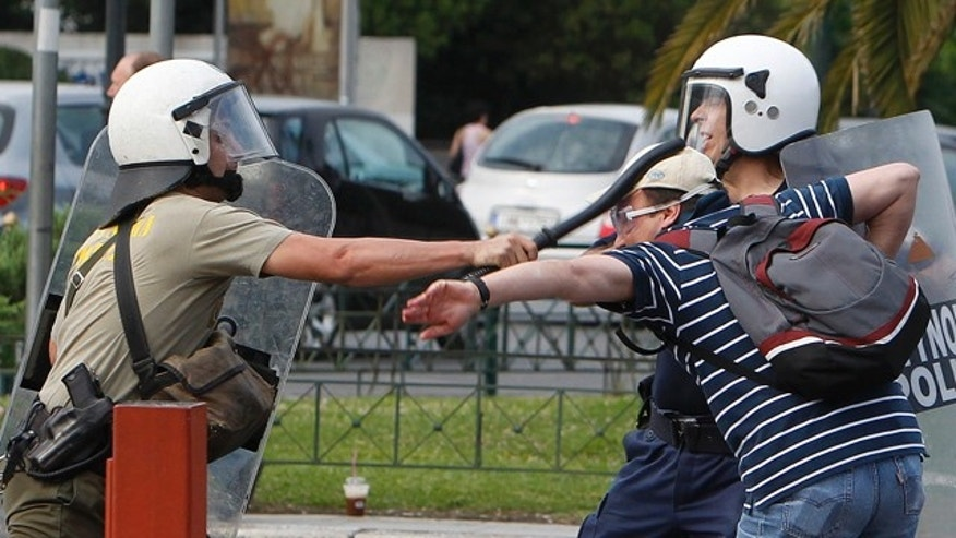 June 29: A riot policeman strikes a demonstrator as protesters try to prevent deputies from reaching the Greek parliament in central Athens.
