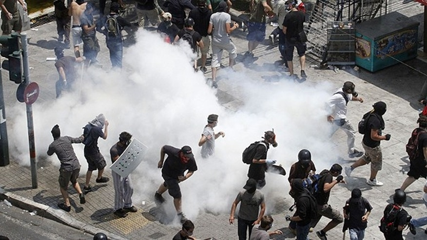 June 28: Demonstrators run away from tear gas during a demo in Athens. Greece's beleaguered government is bracing for a 48-hour general strike as lawmakers debate a new round of austerity reforms designed to win the country additional rescue loans needed avoid bankruptcy.