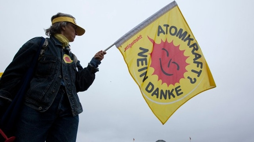 "June 30: An anti-nuclear protester holds a flag reading ""Nuclear power - no thanks"" as she demonstrates in front of the German parliament building in Berlin, Germany."