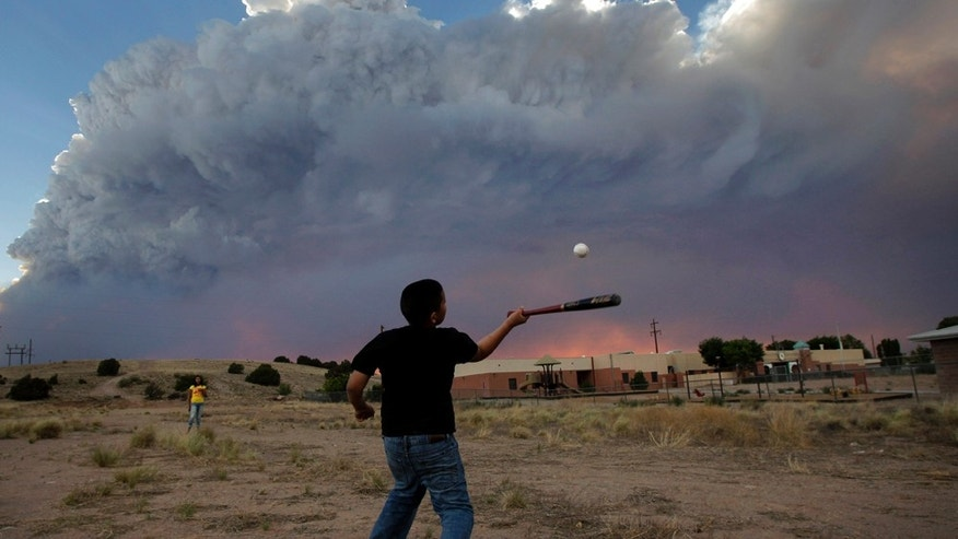 June 29: Alex Lopez, center, plays baseball with his sister Sugey while smoke generated by the Las Conchas fire covers the sky in Espanola, N.M. (AP Photo/Jae C. Hong)