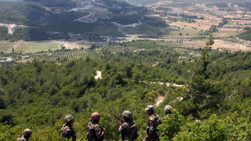 June 29: In this photo taken on a government-organized tour, Syrian soldiers patrol the area along the Syrian-Turkish border in the village of Khirbet al-Jouz in the northern province of Idlib.