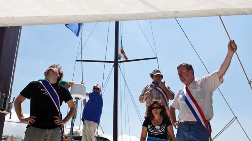 July 4: French activists stand on the deck of their boat moored in Pireaus port, near Athens, Greece. Organizers of a Gaza-bound flotilla said Sunday they have not abandoned their plans to breach Israel's sea blockade of the territory, despite a Greek government ban on their vessels leaving Greek ports.