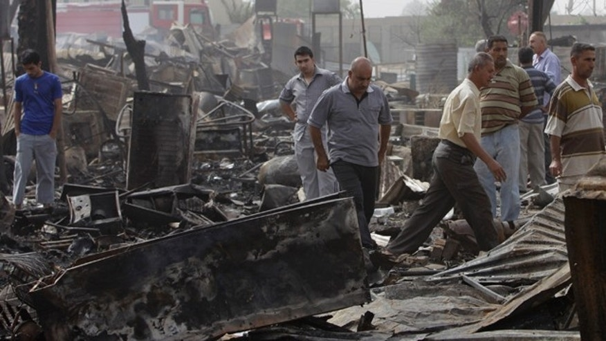 July 5: People inspect a separate scene of rocket attack at a residential complex in Baghdad.