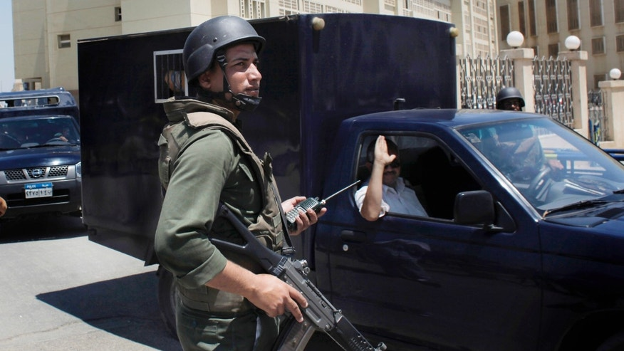 July 5: An Egyptian soldier secures the road as police prisoner vehicles transport three Mubarak-era ministers out of the Supreme State Security Court after attending their trial session in Cairo, Egypt.