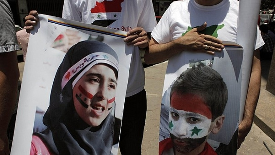 July 5: Two protesters carry posters with pictures of unidentified relatives in Syria, with the Syrian flag colors painted on their faces during an anti-Syrian regime rally near the Syrian embassy in Cairo, Egypt.