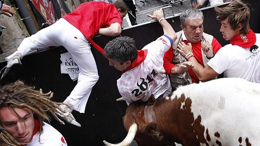 July 7: Revelers are surprised by an angry leading ox, used to drive the fighting bulls during the running of the bulls at the San Fermin fiestas in Pamplona, Spain.