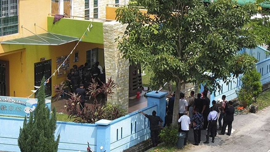 July 7: Malaysian police monitoring outside a kindergarten where a man took some 30 children and teachers captive in Muar, Malaysia.
