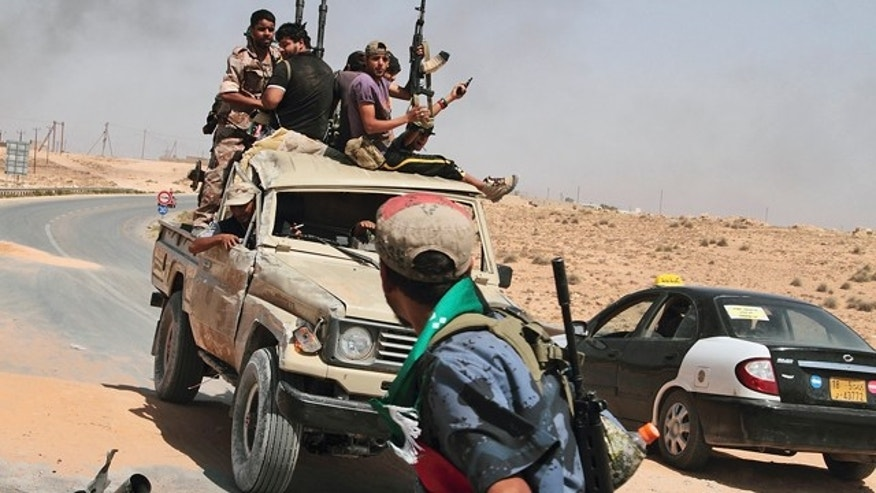 July 6: Rebels are seen on their way back from the frontline after a six-hour battle in which they succeeded to liberate al-Qawalish, Libya.