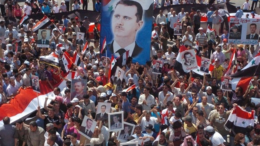 July 6: In this photo released by the Syrian official news agency SANA, pro-Syrian President Bashar Assad demonstrators display posters with his image during a gathering to show their support at Ezraa village in Daraa province, Syria.