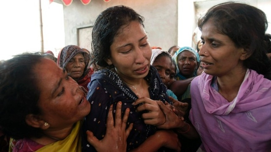 July 8: Women comfort a Pakistani wife who lost her husband after he was fatally shot in Karachi, Pakistan.