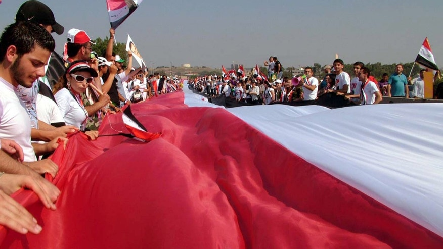 July 10: Thousands of supporters of Syrian President Bashar Assad, carry a gigantic 17,500 yards (16,000 meters) Syrian flag during a pro-Assad demostration, in the Mediterranean city of Latakia, northewest of Damascus, Syria.