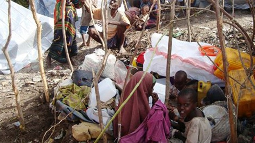 Somalis from southern Somalia, erect  makeshift shelters  in Mogadishu Somalia on Monday July 11, 2011. after fleeing from southern Somalia . Thousands of people have arrived in Mogadishu over the past two weeks seeking assistance and the number is increasing by the day, due to lack of water and food.