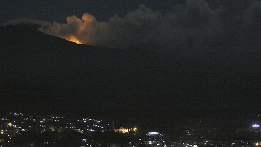 July 15: The glow of lava from Mount Lokon's eruption is seen against the night sky as seen from Manado, North Sulawesi, Indonesia.