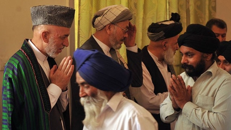 President of Afghanistan Hamid Karzai, left, greets Sikh elders during a funeral for his late brother Ahmad Wali Karzai at the Presidential Palace in Kabul, Friday, July 15, 2011.