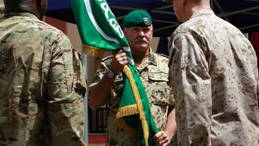 July 18: German Gen. Wolf Langheld, center, Commander NATO Allied Joint Force Command handing over the flag of International Security Assistance Force (ISAF) to the new NATO- led International Security Assistance Force commander in Afghanistan U.S. Gen. John Allen, right, during a changing of command ceremony in  Kabul, Afghanistan.