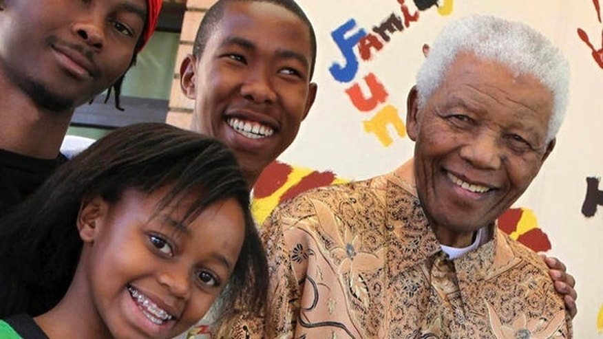 In this 2010 photo, Nelson Mandela, former South African president, right, is with his great-granddaughter Zenani Mandela, front left, Thembela Mandela, back left, and Mbuso Mandela, back right.
