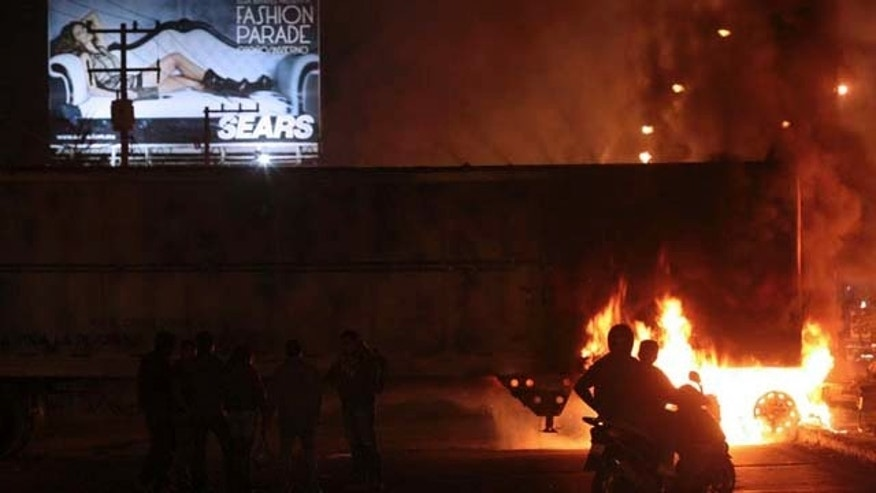 People watch as a truck blocking the road burns Mexico. Friday Nov. 5, 2010.