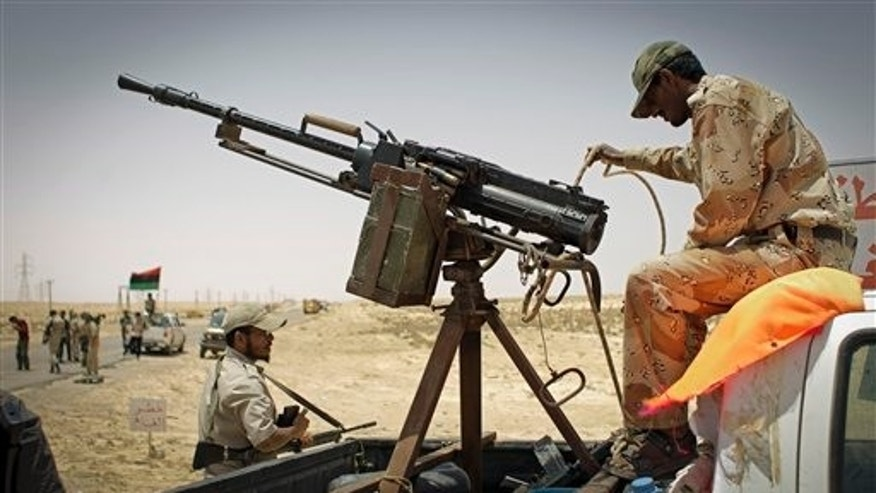 July 19: A Libyan rebel fighter checks a machine gun at the checkpoint some 20 kilometers west from the rebel-held Ajdabiya towards the strategic oil town of Brega, Libya. Government forces shelled rebel positions Tuesday near the strategic oil town of Brega, killing rebel fighters and wounding dozens, a medic said.