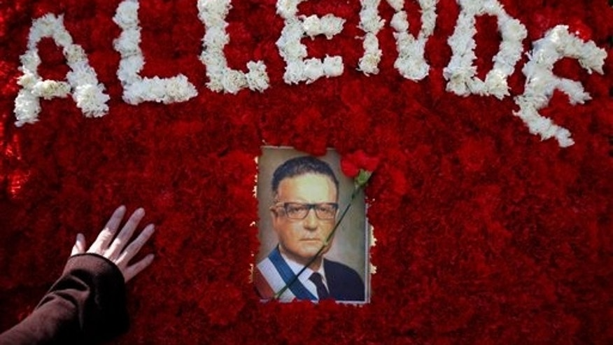 2009: A supporter of Chile's late President Salvador Allende touches a flower arrangement with an image of him during a demonstration outside La Moneda presidential palace in Santiago, Chile.