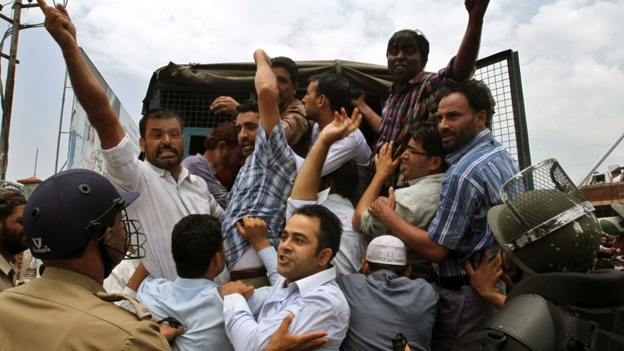 Indian policemen detain Jammu Kashmir state government employees as they shout slogans during a protest in Srinagar, India, Monday, July 18, 2011. The employees demanded payment of arrears in salaries, raising of retirement age and other demands.