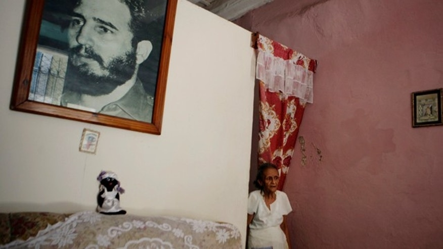 July 18: Margarita Gonzalez is seen next to a photograph of Cuba's leader Fidel Castro in Havana. Fifty years after Fidel Castro's revolution froze property transactions, a severe housing crisis has stubbornly resisted repeated government attempts to fix the problem.  (AP Photo/Javier Galeano)