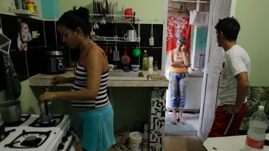July 14: Claudia Martinez, who is pregnant, prepares coffee for her husband, Malvin Cabrera, and her mother, Niurka Gomez, at the couple's home in Havana. (AP Photo/Javier Galeano)