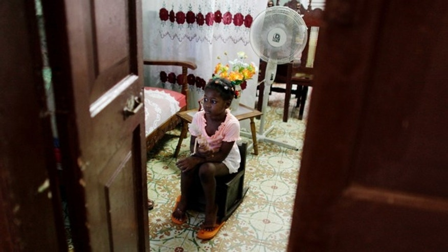 July 14: Aylenis Planche, 4, watches television inside her home in Havana. Fifty years after Fidel Castro's revolution froze property transactions, a severe housing crisis has stubbornly resisted repeated government attempts to fix the problem. (AP Photo/Javier Galeano)