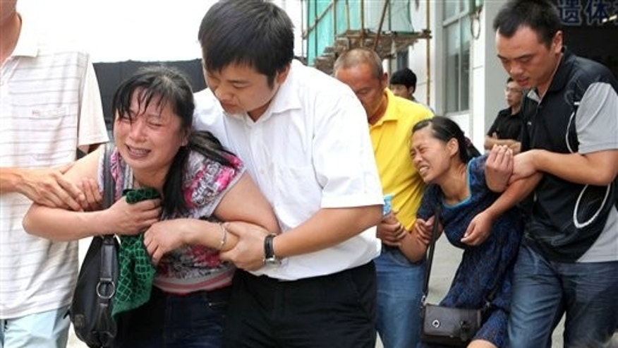 July 26: Relatives of the victims in Saturday's train crash cry after seeing the bodies of their loved ones in a funeral home in Wenzhou, east China's Zhejiang Province.