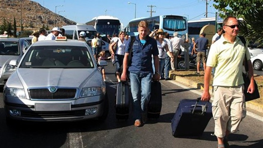 Foreign tourists carrying their luggage walk to the airport of Iraklion, as striking taxi owners block access to the terminal for all buses, on the island of Crete, Greece, Monday Aug. 1, 2011.