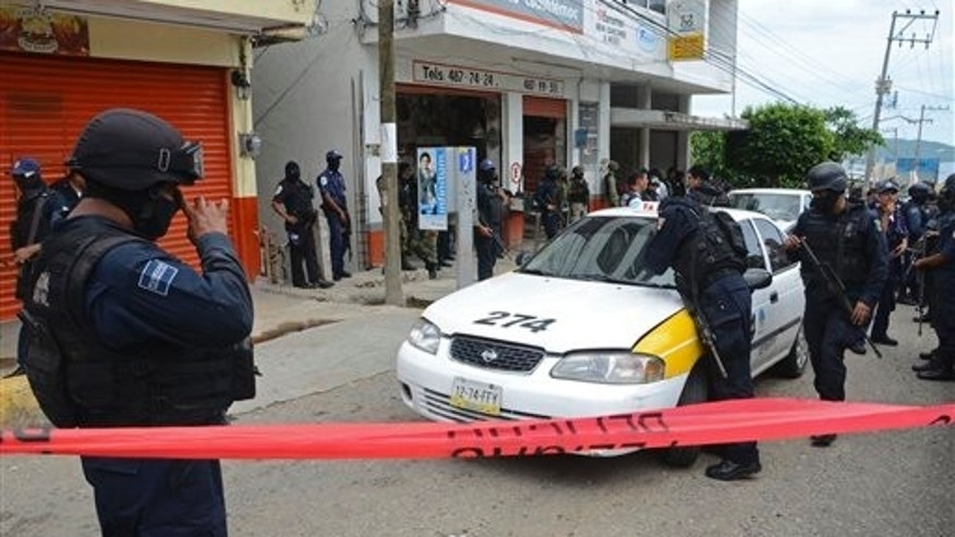 Federal police inspect a taxi in the Pacific resort city of Acapulco, Mexico, Saturday July 16, 2011.  Two men with multiple gunshot wounds with their hands tied behind their backs were found inside the vehicle's trunk.