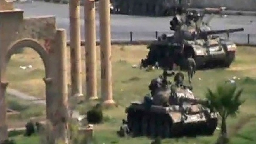 Aug. 1: In this image made from amateur video released by the so-called Shams News Network, a loosely organized anti-Assad group and accessed via The Associated Press Television News, military armored vehicles are seen in the central city of Hama, Syria.
