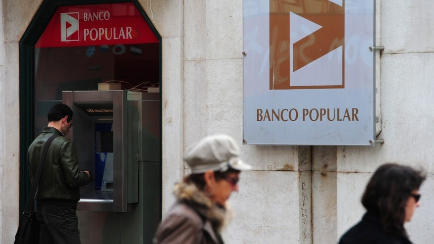 Mar 29:  A man stands behind a cash machine of the Banco Popular in Lisbon, Portugal.