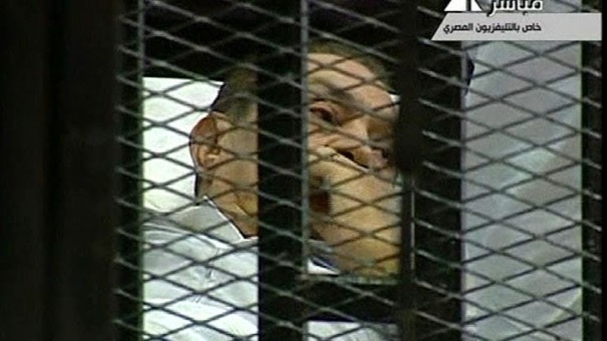 Aug. 3: This video image taken from Egyptian State Television shows 83-year-old Hosni Mubarak laying on a hospital bed inside a cage of mesh and iron bars in a Cairo courtroom as his historic trial began on charges of corruption and ordering the killing of protesters during the uprising that ousted him.