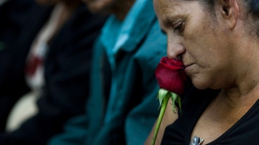 A woman holds a rose as she waits for the sentence during a trial in Guatemala City, Tuesday, Aug. 2, 2011. The court sentenced three former special forces soldiers to 6,060 years in prison each for the massacre of more than 200 men, women and children, one of hundreds that occurred during Guatemala's 36-year civil war, which ended in 1996. Some 240,000 people, mostly Mayan Indians, vanished or died. (AP Photo/Rodrigo Abd)