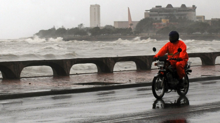 A motorcyclist rides along the Santo Domingo waterfront as Tropical Storm Emily approaches the shores of the Dominican Republic.