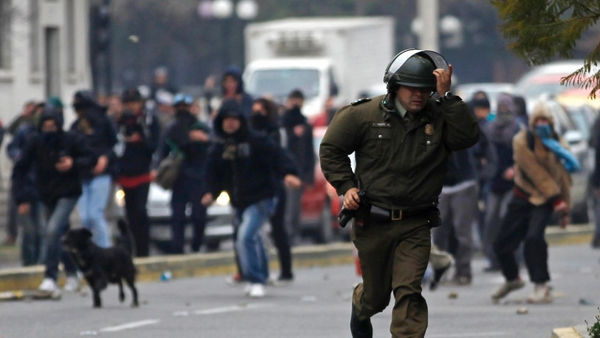 A police officer runs from hooded protestors throwing stones during student demonstrations in Santiago, Chile, Thursday Aug. 4, 2011.