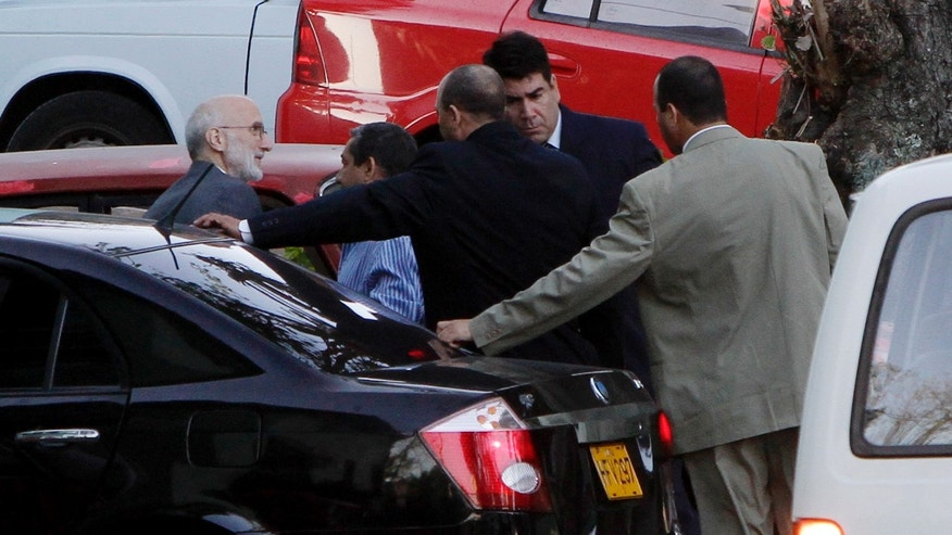 U.S. government contractor Alan Gross, left, is surrounded by security forces as he arrives for his trial in Havana, Cuba. Gross, a 61-year-old Maryland native, was arrested in December 2009 and charged with undermining Cuba's government by bringing communications equipment onto the island illegally.