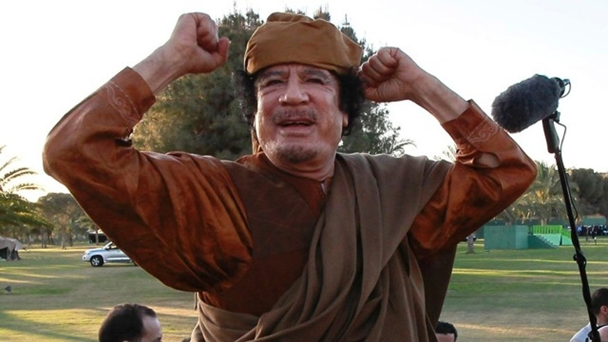 April 10: Libyan leader Muammar al-Qaddafi gestures to his supporters in Tripoli, Libya.