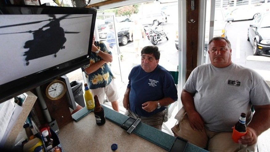 Aug. 6: Virginia Beach residents Tom Hall, left, and Mark Janik, center, watch as news about the Navy Seal Team Six helicopter accident is displayed on a television at a bar in Virginia Beach , Va. The headquarters for the Navy Seal Team Six is located in Virgina Beach.