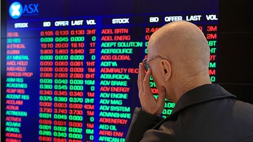 Aug. 8: Rudolf Oultz watches the display board at the Australia Stock Exchange in Sydney. Australian and New Zealand markets opened lower in reaction to ratings agency Standard and Poor's downgrading of the United States government credit rating from AAA to AA+.