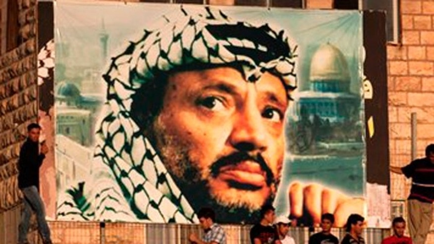 In this July 28, 2011 file photo, Palestinian soccer fans sit under a large banner showing late Palestinian leader Yasser Arafat during a World Cup qualifier game against Thailand in the West Bank city of Ramallah.