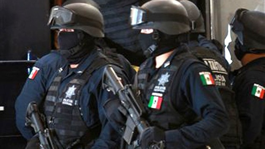 Police officers escort a suspect before his presentation to the media in Mexico City, Tuesday, Aug. 2, 2011.