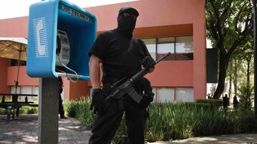 A police officer stands guard after a mail bomb exploded at the Tecnologico de Monterey University, on the outskirts of Mexico City, Monday, Aug. 8, 2011. According to authorities of the university, the explosion injured two professors. (AP Photo/Arnulfo Franco)