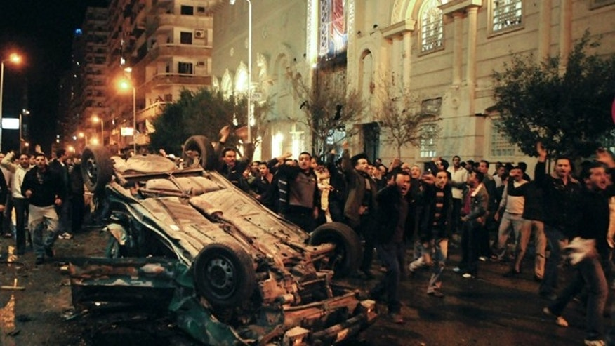 Jan. 1, 2011: Worshippers shout around an exploded car in front of a Coptic Christian church in the Egyptian city of Alexandria, Egypt.